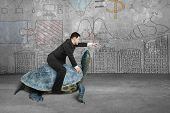 foto of indications  - Businessman riding turtle and indicating with finger in the concrete room and business concept doodles wall background - JPG