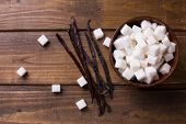 picture of sugar cube  - White sugar cubes in bowl and vanilla beans on dark wooden background - JPG