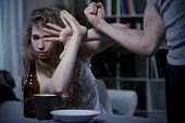 picture of defender  - Terrified young woman defending herself from violent husband - JPG