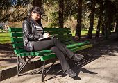 foto of black pants  - young beautiful woman in a black leather jacket and black pants sitting on a park bench writing a pen in notebook on sunny spring day - JPG