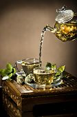 picture of teapot  - vertical photo of the glass teapot flow green tea in cup on brown background tea ceremony - JPG