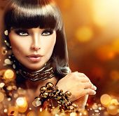 stock photo of golden  - Fashion model brunette girl with golden accessories over gold shiny background - JPG