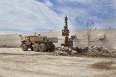 stock photo of dump_truck  - A front end loader scoops rubble from a demolished building and loads it into a waiting dump truck - JPG