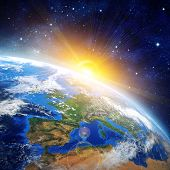 stock photo of outer  - High definition picture of planet earth in outer space with the rising sun - JPG