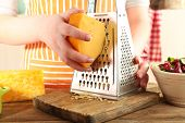foto of grating  - Closeup of female hands grating cheese - JPG