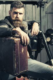 foto of biker  - Serious unshaven male biker in leather jacket sitting near motorcycle in garage with big brown old briefcase looking forward on workshop background vertical picture - JPG