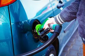 picture of fuel pump  - man pumping gasoline fuel in car at gas station - JPG