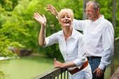 picture of say goodbye  - Mature or senior couple at a summer day standing on a bridge waving their hands as if to say goodbye to somebody - JPG