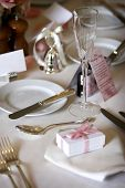 foto of wedding table decor  - table setting for a wedding or dinner event very shallow depth of field with the focus on the glass blank name card in the background - JPG