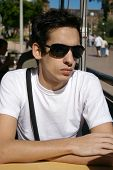 Young Man Sitting With Sun Glasses