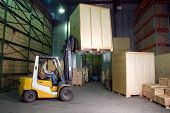 picture of lift truck  - man working on the truck in the warehouse - JPG