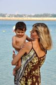 Mother Holding Her Son On Hands At Beach