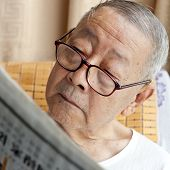 A Senior Man Is Reading Newspaper