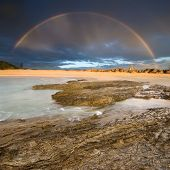 rainbow with rock in foreground at cloudy morning