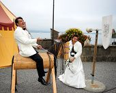 foto of jousting  - A smiling groom is sitting on a wooden horse in a pretend medieval joust as the brides knight - JPG