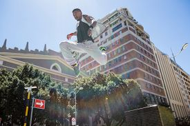 image of parkour  - Athletic man doing parkour in the city on a sunny day - JPG
