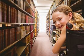 picture of wheelchair  - Portrait of cute girl sitting in wheelchair against close up of a bookshelf - JPG