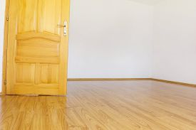 stock photo of laminate  - empty room with white walls and wooden laminate and open wooden door - JPG