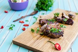 pic of radish  - Grilled pork steak cutting in stripes on chopping board close-up served with salad of radishes cucumbers and fresh goat cheese with red hot chili peppers and buch of green parsley around wooden spoon over styled wooden turquoise table ** Note: Shallow de - JPG
