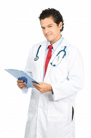 foto of empathy  - A smiling compassionate male latino doctor in white lab coat looking at camera head tilted listening and holding medical charts displaying empathy and compassion - JPG