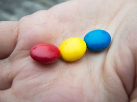 stock photo of bonbon  - sweet tricolor chocolate bonbons in a hand - JPG
