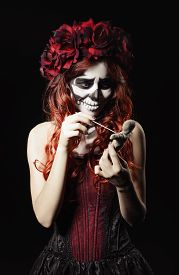 foto of sugar skulls  - Young voodoo witch with calavera makeup  - JPG