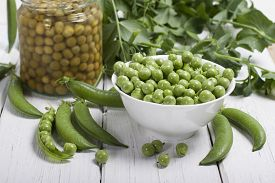 foto of pea  - Fresh green peas in a white bowl canned peas in a glass jar and some pea pods on a white table - JPG