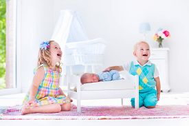 stock photo of bassinet  - Kids playing with newborn baby brother - JPG