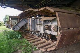 stock photo of backhoe  - Rusty wheels of big backhoe in nature - JPG