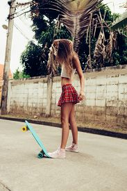 foto of mini-skirt  - Skinny young girl with sporty butt in a red tartan mini skirt with blue penny skateboard shortboard stands on the tropical street and style her hair - JPG
