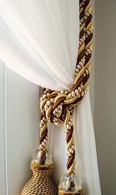 stock photo of tassels  - Dual tassels on curtain at main window - JPG