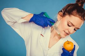 pic of modification  - Scientist doctor injecting apple with syringe - JPG