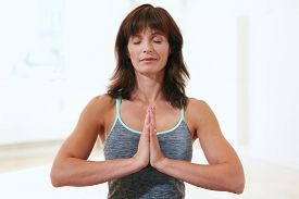picture of mudra  - Portrait of a beautiful mature woman sitting in Anjali Mudra yoga pose at the gym meditating - JPG