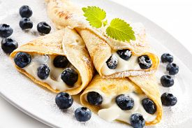 picture of crepes  - Crepes with blueberries and cream on white background  - JPG