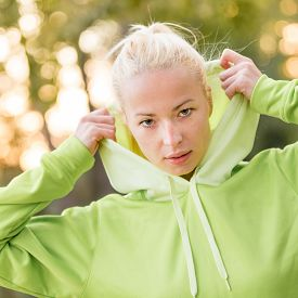 picture of hoodie  - Portrait of attractive confident sporty woman wearing fashionable green hoodie while training in the nature - JPG