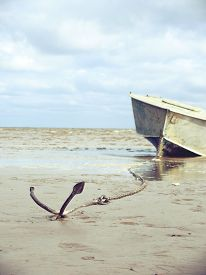 foto of anchor  - anchored on the shore with boat in the background - JPG