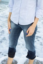foto of wet pants  - Woman in jeans and shirt standing in sea water barefoot - JPG