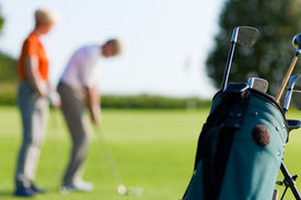 stock photo of golf bag  - Mature or senior couple playing golf - JPG