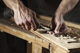 picture of chisel  - Closeup of a carpenter hands working with a chisel and carving tools on wooden workbench - JPG
