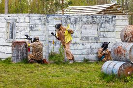 image of paintball  - Three men in dynamic situation with paintball flag - JPG