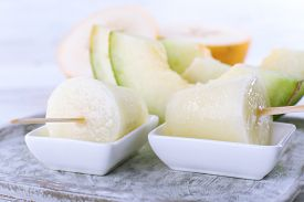 picture of lolli  - Melon ice lolly on wooden table - JPG