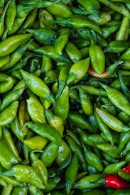 picture of red hot chilli peppers  - Heap of red and green Cayenne pepper is also called Guinea spice cow-horn pepper red hot chili pepper aleva or bird pepper for retail sale on fresh food market ** Note: Visible grain at 100%, best at smaller sizes - JPG