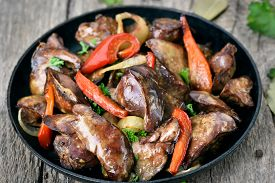 foto of liver fry  - Grilled chicken liver in frying pan on wooden table close up view - JPG