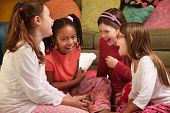 stock photo of foursome  - Group of four little girls in pajamas laugh at a sleepover - JPG