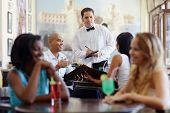 People Ordering Meal To Waiter In Restaurant