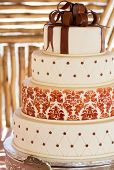 stock photo of three tier  - Layered white wedding cake with chocolate detail on silver serving dish - JPG