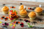 food, baking and holidays concept - cupcakes or frosted muffins with halloween party decorations and poster