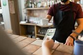payment, people and service concept - man or bartender with cup serving customer paying money at cof poster