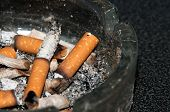 Stubs in an ashtray. The smoking it is harm for health. It is time to stop