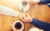 people, love, romance and dating concept - close up of happy couple drinking tea and holding hands a poster